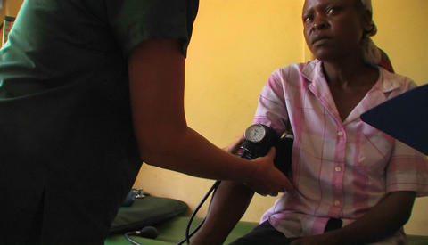 A medical worker checks the blood pressure of an African woman Footage