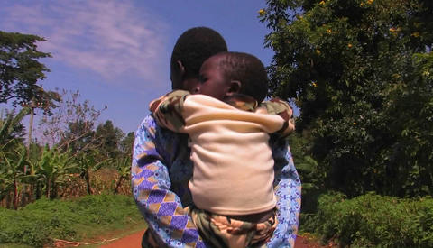 A mother carries a child on a rural dirt road Footage