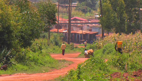 People in a small village walk down a red dirt road Stock Video Footage