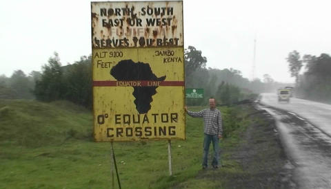 A man stands next to a sign announcing the equator crossing Stock Video Footage