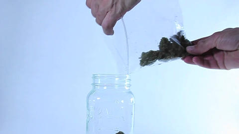A man puts grass in a jar Stock Video Footage