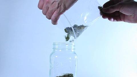 A man puts grass in a jar Footage