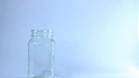 A person puts marijuana in a glass jar from a plastic bag Stock Video Footage