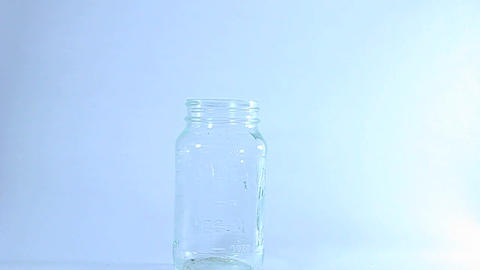 Hands transfer marijuana from a plastic bag to a glass jar Stock Video Footage