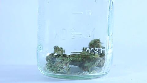 A person drops dried marijuana buds into a glass jar Stock Video Footage
