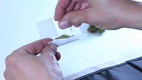 A man rolls a marijuana cigarette Stock Video Footage