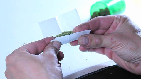 A person rolls a marijuana cigarette Stock Video Footage