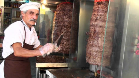 A butcher sharpens his knife before two hunks of spinning... Stock Video Footage