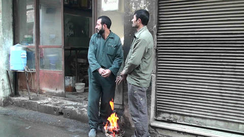 Two men warm their hands over a small fire on a street in... Stock Video Footage