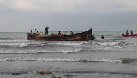 Fishermen on a traditional style boat and motorboats off... Stock Video Footage