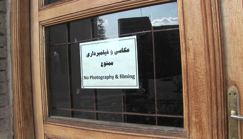 A sign on a window in Iran warns visitors that photography and filming in prohibited Footage