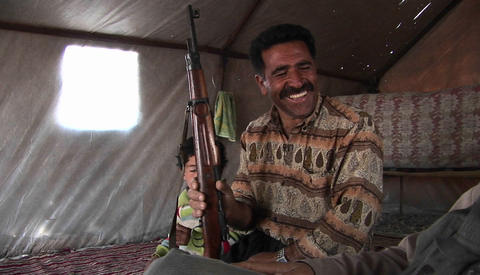 A man holds an assault rifle in a tent in Iran Live Action