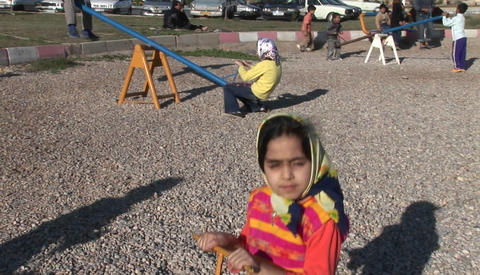 Children play on a see-saw in Iran Footage