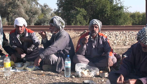 Men wearing the traditional muslim headdress, or keffiyeh, sit by a fire outside in Iran Footage
