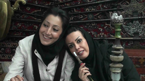 Women in headscarfs smoke a hookah pipe in a cafe in Iran Footage