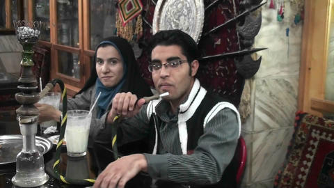 A woman wearing a headscarf and a man smoke a hookah pipe... Stock Video Footage