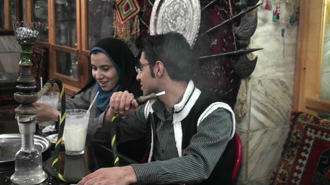 A woman wearing a headscarf and a man smoke a hookah pipe in an outdoor cafe in Iran Footage