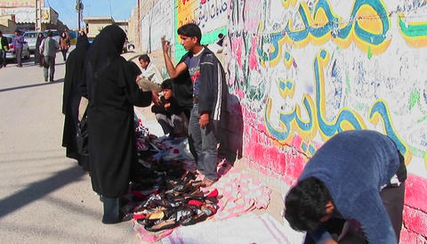 A women wearing chadors buy from vendors near a wall... Stock Video Footage