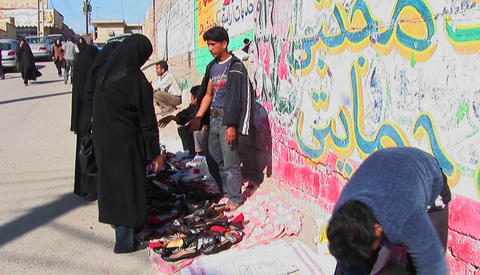 A women wearing chadors buy from vendors near a wall covered in graffiti in an urban area Footage