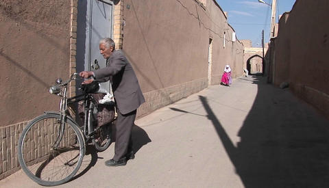 A man leans a bicycle against a wall in an ancient alley way in Iran Footage