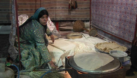 A woman wearing a headscarf bakes lavash bread on a... Stock Video Footage