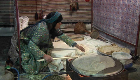 A woman wearing a headscarf bakes lavash bread on a tandori oven. Lavash is a traditional flatbread Footage