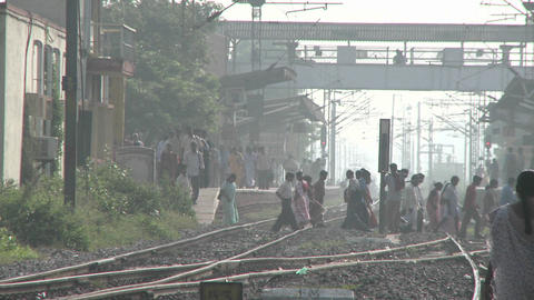 People walk back and forth across railroad tracks Footage