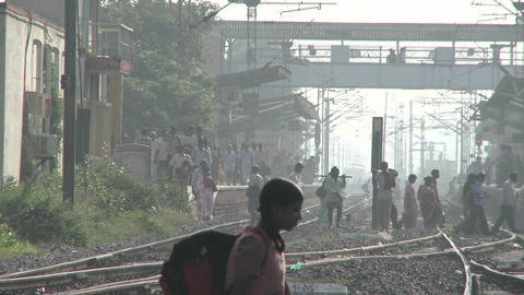 People walk back and forth across railroad tracks Stock Video Footage