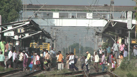 Crowds of people walking across a train-station's tracks Footage