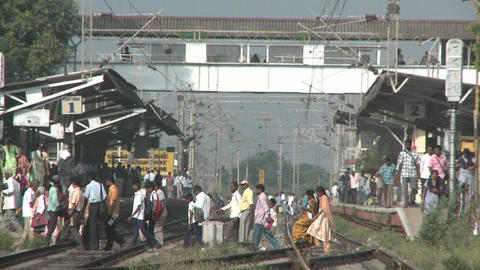 Crowds of people walking across a train-station's tracks Stock Video Footage