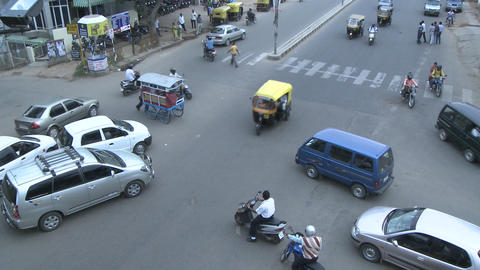 Vehicles and pedestrians travel through a busy intersection Stock Video Footage