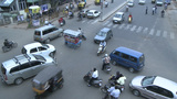 Vehicles and pedestrians travel through a busy intersection Footage