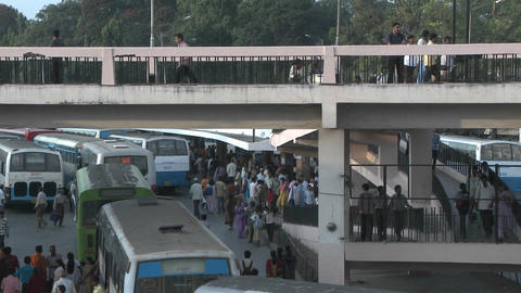 People gather in a bus station, getting on and off buses and crossing an overhead walkway Footage