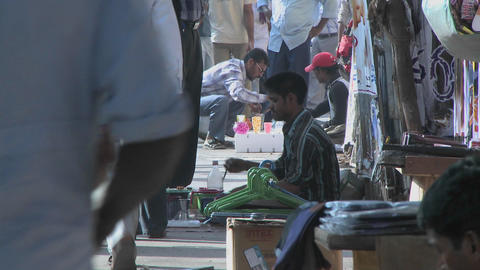 Street vendors sell their wares on a sidewalk in India Footage