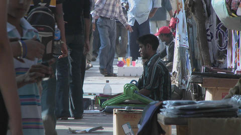 Street vendors sell their wares on a sidewalk in India Stock Video Footage