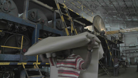 A man carries a large pile of paper over his head through a manufacturing plant Footage