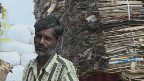 Older man stares towards camera, while man adds another bale of cardboard behind him Footage