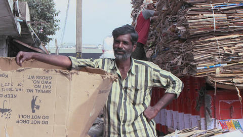 A man is leaning against a big open cardboard box Footage