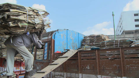 An older man carries a heavy load of cardboard up a ramp Stock Video Footage