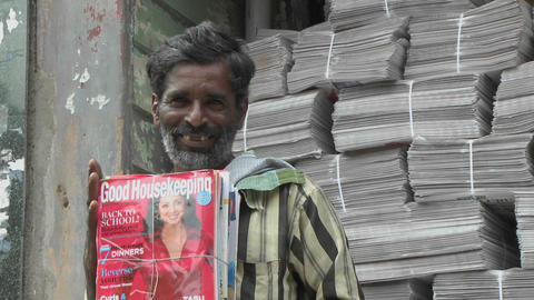 A man is smiling while holding a bundle of magazines Stock Video Footage