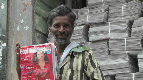A man is smiling while holding a bundle of magazines Footage