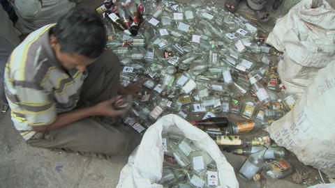 A man is sorting glass bottles on the ground Stock Video Footage