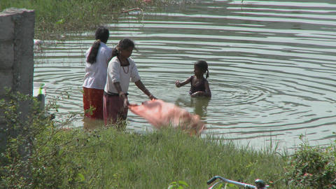 Two young woman wash clothes while a child plays in the... Stock Video Footage