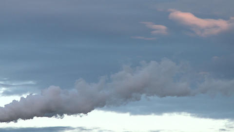 Water vapor floats in the wind which moves it along with the clouds in the background, a pastel colo Footage