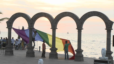 Gay pride flag being hung from the arches down town in... Stock Video Footage
