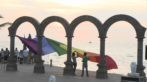 Gay pride flag being hung from the arches down town in Puerto Vallarta, beach resort which has a lar Footage