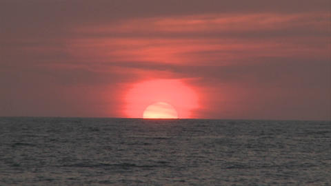Sun sets in the distance in Puerto Vallarta, Mexico, at a beach resort. Orange sky, blue water with Footage