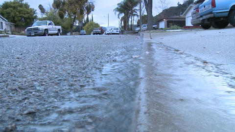Water running off the sidewalk after a rain in Oak View, California Footage