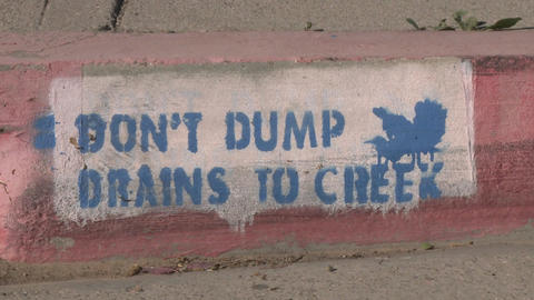 Pan of a Don't Dump Drains to Creek sign in Ojai, California Stock Video Footage