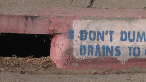 Pan of a Don't Dump Drains to Creek sign in Ojai, California Footage